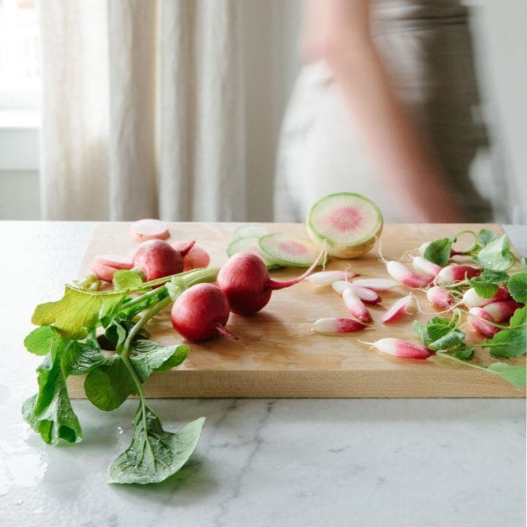 Red radishes on a wood cutting board, with a woman walking by through the kitchen
