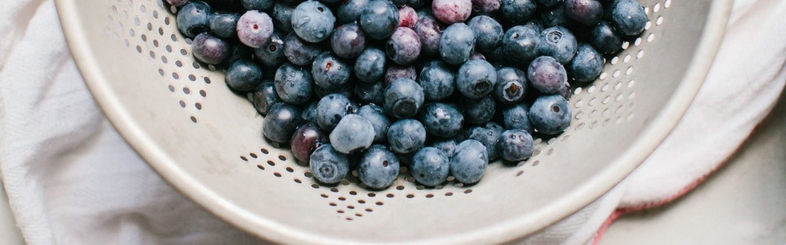 Blueberries in a while bowl about to be washed for making blueberry pie