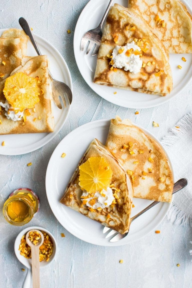 Breakfast crepes and oranges on white plate on marble kitchen counter