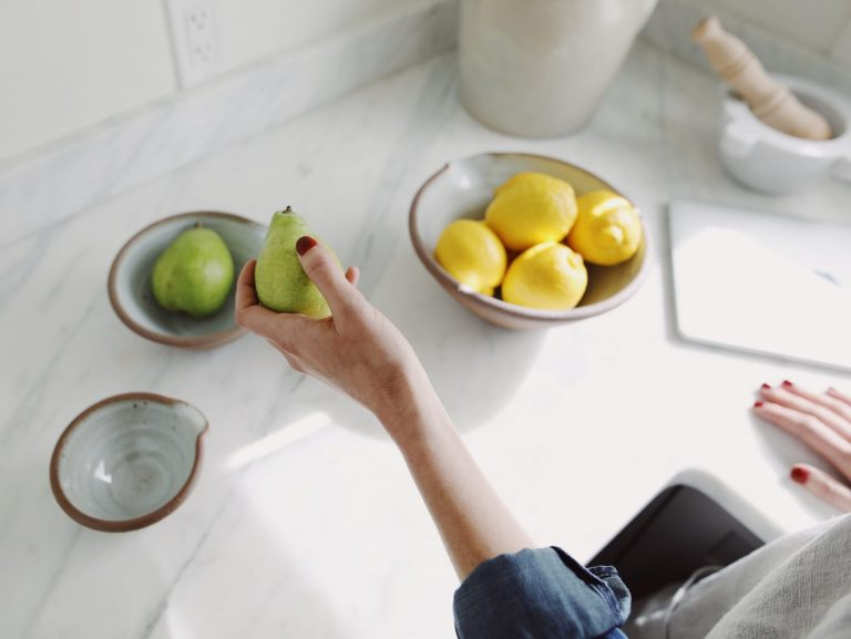Photo of a woman's left hand holding a green pear. Bowl of lemons and a MAC computer are sitting on the kitchen counter
