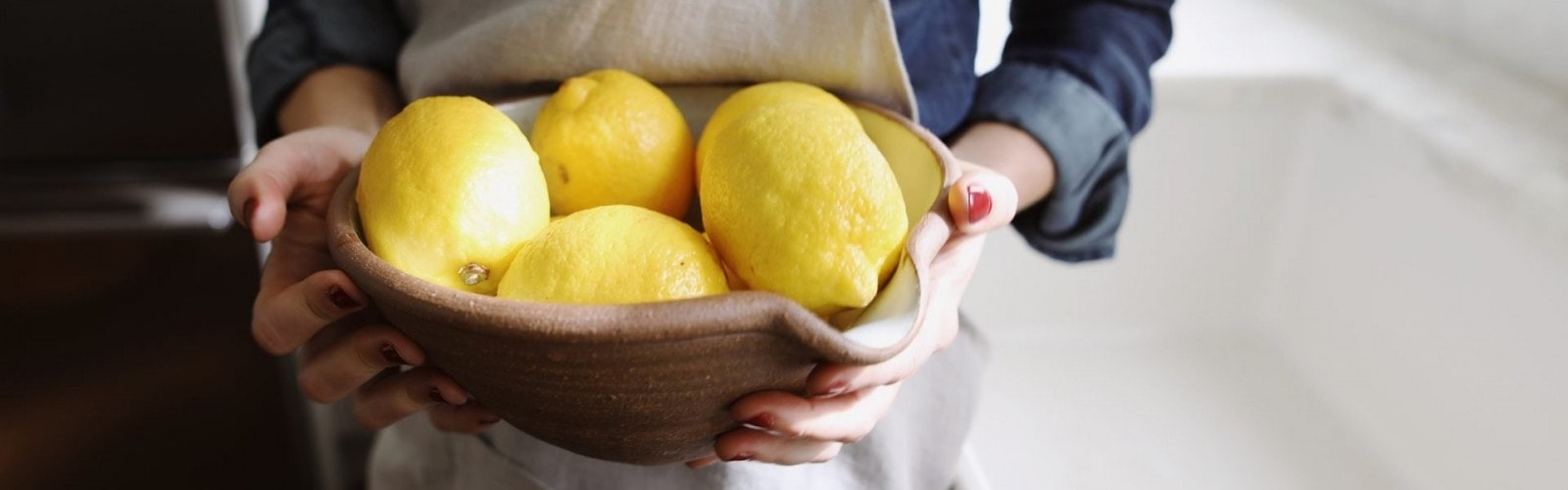 Photo of a woman in an apron holding a bowl full of lemons while standing next to a sink in a kitchen