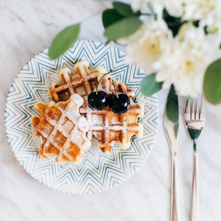 Waffles on a blue plate, topped with red cherries. Fork and knife off to the side