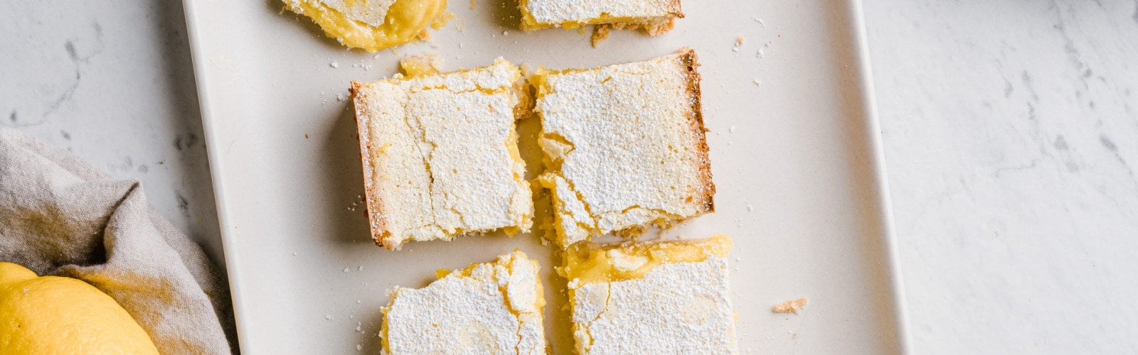 Organic and gluten free lemon bars ready-to-serve and one already nibbled on, placed on a marble counter top
