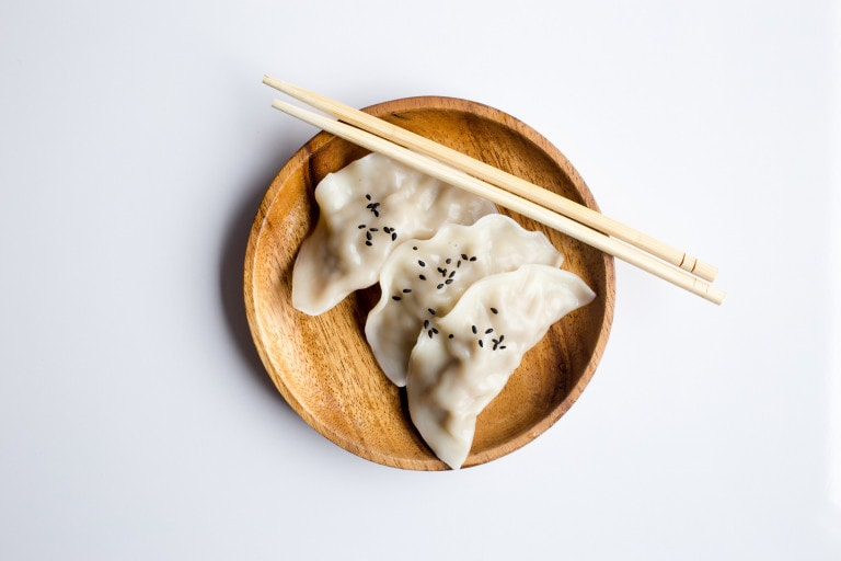 White dumplings on a bamboo plate, with chopsticks on the side